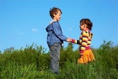 Miúdos nas mãos verdes da terra arrendada do prado Fotografia de Stock