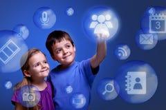 Miúdos que alcançam aplicações da nuvem Fotos de Stock
