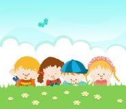 Miúdos que encontram-se na grama Imagens de Stock