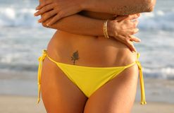 Midriff of a Woman with a Rose Tattoo. Midriff of a Woman in a Yellow Bikini with a Rose Tattoo on the Beach royalty free stock images