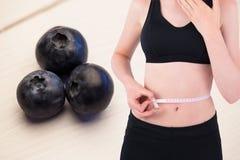 Midsection της γυναίκας που μετρά τη μέση κατά των φρούτων στο υπόβαθρο Στοκ Φωτογραφίες