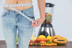 Midsection της γυναίκας που μετρά τη μέση με το juicer και τα φρούτα στο υπόβαθρο Στοκ εικόνα με δικαίωμα ελεύθερης χρήσης
