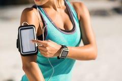 Midsection της γυναίκας που χρησιμοποιεί το smartphone armband Στοκ Εικόνες