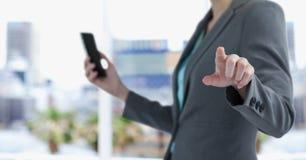 Midsection της επιχειρηματία που κρατά το έξυπνο τηλέφωνο δείχνοντας στην πόλη Στοκ Εικόνες