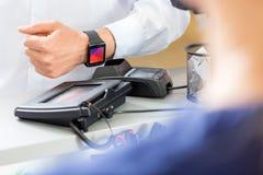 Midsection της πληρωμής πελατών μέσω Smartwatch στο μετρητή στο Π στοκ φωτογραφίες με δικαίωμα ελεύθερης χρήσης