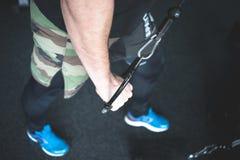 Midsection του νεαρού άνδρα που χρησιμοποιεί την τροχαλία στη γυμναστική στοκ εικόνες
