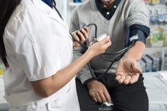 Midsection του φαρμακοποιού που ελέγχει την υπομονετική πίεση του αίματος ` s στοκ εικόνες