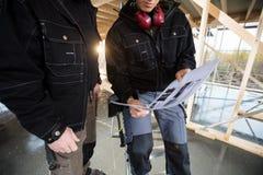 Midsection των ξυλουργών με το σχέδιο επί του τόπου Στοκ Φωτογραφία