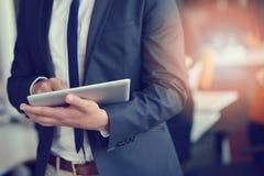 Midsection бизнесмена используя цифровую таблетку в офисе Стоковое фото RF