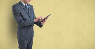 Midsection бизнесмена используя цифровую таблетку над покрашенной предпосылкой Стоковое Изображение RF