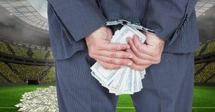 Midsection бизнесмена с наручниками и деньгами на футбольном стадионе представляя коррупцию Стоковая Фотография RF