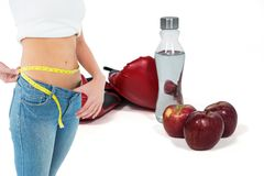 Midsection женщины в свободных джинсах измеряя талию с яблоками и перчатки бокса с задней частью бутылки внутри Стоковые Изображения