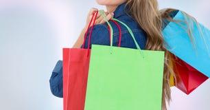Midsection женщины держа хозяйственные сумки против белой предпосылки Стоковое фото RF