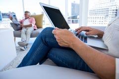 Midsection женщины используя компьтер-книжку пока газета чтения человека Стоковые Изображения