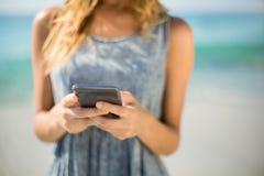 Midsection женщины используя мобильный телефон на пляже Стоковое фото RF