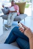 Midsection женщины используя телефон пока газета чтения человека Стоковые Фото