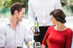 Midsection кельнера показывая бутылку вина к парам Стоковая Фотография