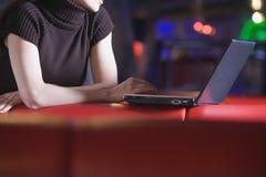 Midsection коммерсантки используя компьтер-книжку в кафе Стоковые Изображения