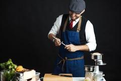 Midsection мужского шеф-повара точить нож в коммерчески кухне стоковое фото rf