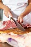Midsection мясника отрезая свежее сырое мясо Стоковое Изображение RF