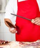 Midsection мясника точить нож стоковые фото