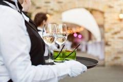Midsection профессиональных кельнеров в равномерном вине сервировки, коктеили и закуски во время ресторанного обслуживании шведск стоковое изображение