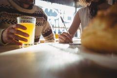 Midsection человека при женщина имея сок в кафе Стоковые Изображения