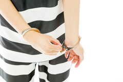Midsection of an Asian young woman in prisoners uniform opening handcuffs Royalty Free Stock Images