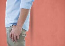 Midsection av affärsmannen med handen i fack över persikabakgrund Arkivfoton