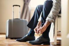 Midsection av affärsmannen på en affärstur som sitter i ett hotellrum som binder skosnöre royaltyfria foton