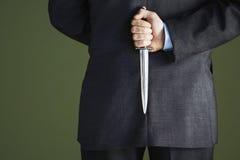 Midsection av affärsmanHolding Knife Behind baksida Royaltyfri Bild