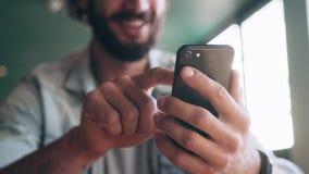 Midsection av att le bloggeren som använder den smarta telefonen arkivfilmer
