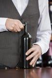 Midsection av bartendern Opening Wine Bottle royaltyfria bilder