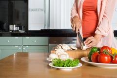 Midsection av bitande grönsaker för kvinna på diskbänken arkivfoto