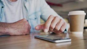 Midsection av bloggeren som använder den smarta telefonen på tabellen stock video