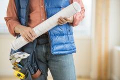 Midsection av byggnadsarbetaren Holding Blueprint Arkivfoton