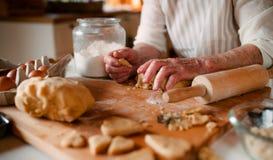 Midsection av den gamla kvinnan som hemma gör kakor i ett kök arkivfoton