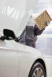 Midsection av den manliga underhållsteknikern som reparerar bilen i billager Arkivbild