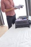 Midsection av den unga affärsmannen som tar skjortan från resväskan i hotellrum Arkivbilder