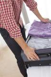 Midsection av den unga mannen som packar upp resväskan i hotellrum Royaltyfri Foto