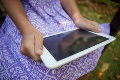 Midsection av flickan som rymmer den digitala minnestavlan, medan sitta på bänk royaltyfria bilder