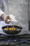 Midsection av kocken Cooking Food fotografering för bildbyråer