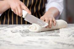 Midsection av kocken Cutting Rolled Dough i kök arkivfoton