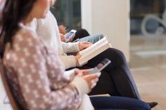 Midsection av kvinnaläseboken i väntande område för flygplats Royaltyfri Bild
