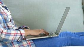Midsection av kvinnan som använder bärbara datorn som ligger på soffan arkivfilmer