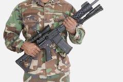 Midsection av soldaten för USA som Marine Corps rymmer geväret för anfall M4 över grå bakgrund Arkivbild