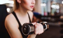 Midsection av unga flickan eller kvinnan med hantlar som gör genomkörare i en idrottshall royaltyfri foto