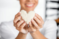 Midsection Of Baker Holding Heart Shape Dough. Midsection of young female baker holding heart shape dough in bakery stock image