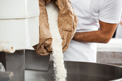 Midsection Of Baker Pouring Flour In Kneading Machine Stock Photos