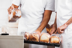 Midsection Of Baker's With Packed Bread Loaves In Bakery Stock Images